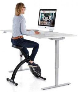 Dame syklende på svart Velo kontorsykkel med hev-senk skrivebord og dataskjerm