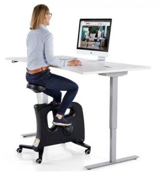 Dame syklende på svart Velo Premium kontorsykkel med hev-senk skrivebord og dataskjerm